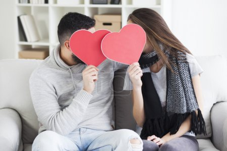 couple kissing behind paper hearts