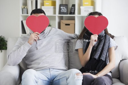 Photo pour Jeune couple cachant leurs visages derrière des coeurs de papier - image libre de droit