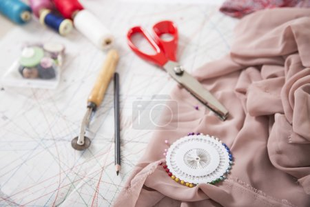Sewing background. Sewing accessories and on a paper pattern.