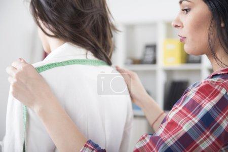 Dressmaker is measuring female customer in her sewing atelier. Tailor measuring women