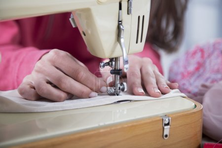 Woman's hands behind her sewing