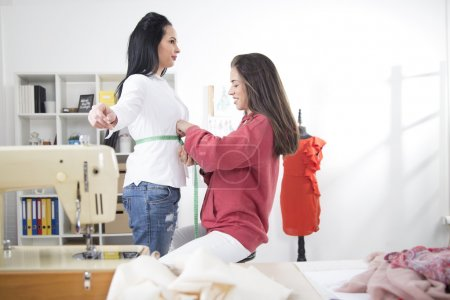 Dressmaker is measuring female customer