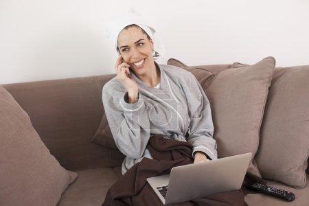 Photo pour Femme en peignoir travaillant sur ordinateur portable et parlant au téléphone dans le salon - image libre de droit