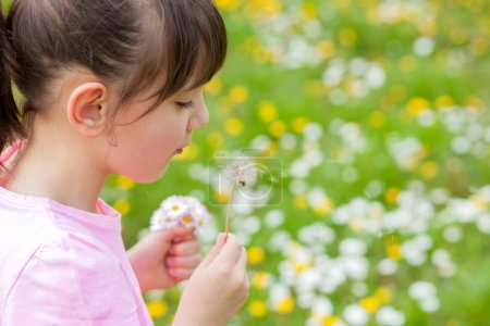 girl blowing dandelion in the park