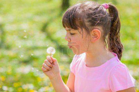 girl blowing dandelion in the park