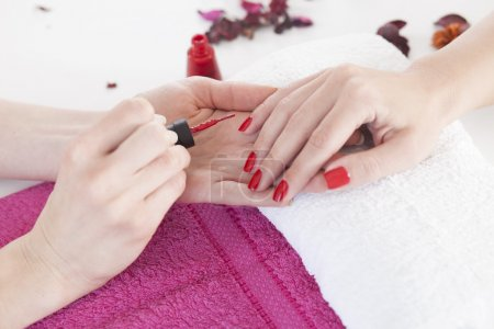 Woman applying red nails