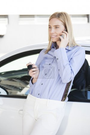 Beautiful blonde women talking on the phone with cars keys in her hand