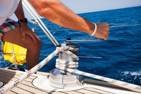 Sailing crew member pulling rope