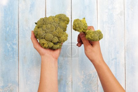Broccoli in hands with wooden table