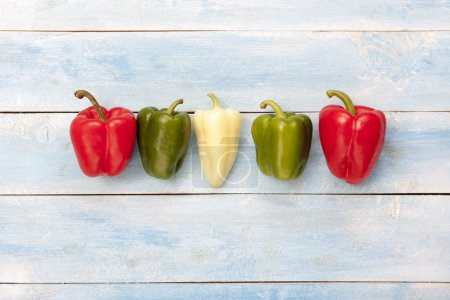 Colorful peppers on a blue wooden board, top view...