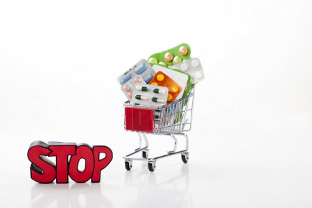 Drugs and pills in supermarket trolley with sign stop