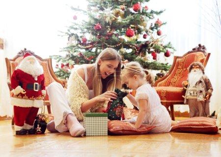 Photo pour Maman et fille assis devant une cheminée - image libre de droit