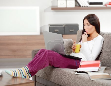 Photo for Beautiful brunette sitting on a couch in the living room with lap top drinking orange juce - Royalty Free Image