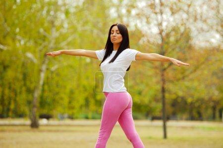 Photo pour Jeune femme sportive se réchauffe en faisant des exercices d'étirement dans un parc. Profondeur de champ faible . - image libre de droit