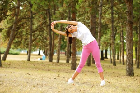 Woman doing stretching exercises in park