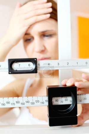 Photo for Young woman regret on a medical weight scale - Royalty Free Image