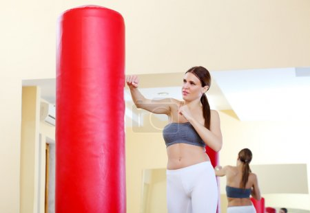 Woman practicing tae bo on red sack