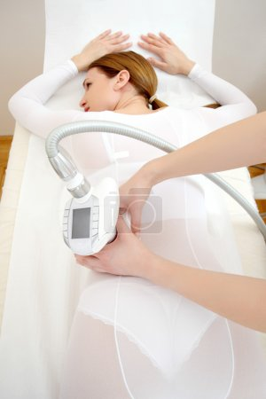 Woman having a treatment against cellulite with LPG machine