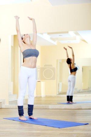 Photo pour Fille faire des exercices d'yoga dans le gymnase - image libre de droit