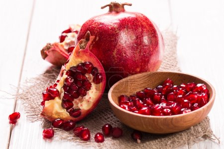 Some red juicy pomegranate, whole and broken, on rustic wooden table