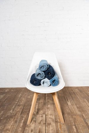 Photo for White chair with rolled denim clothing on wooden floor near brick wall - Royalty Free Image