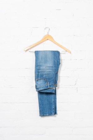 Photo pour Cintre avec jeans bleus près du mur de briques blanches - image libre de droit