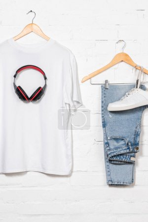 blue jeans, white t-shirt, sneaker and wireless headphones on hangers near brick wall