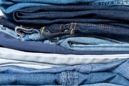 Photo pour Vue rapprochée des vêtements empilés en denim bleu - image libre de droit