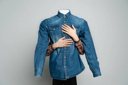 cropped view of woman embracing mannequin in blue denim shirt on grey