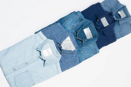 top view of various denim shirts on white background