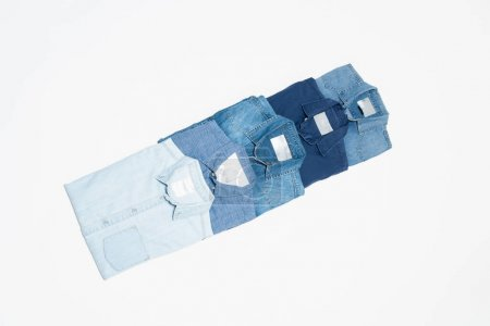 flat lay of blue denim shirts on white background, top view