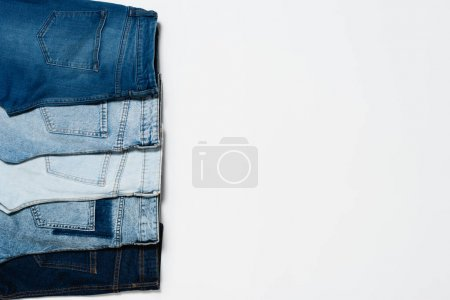 top view of various blue jeans on white background with copy space