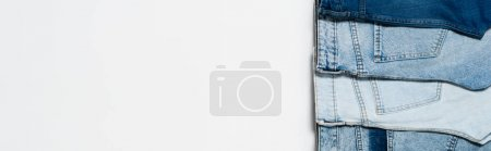 Photo for Vertical row of different blue jeans on white background, top view, banner - Royalty Free Image