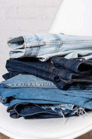 Photo pour Vue rapprochée de jeans bleus empilés sur chaise blanche - image libre de droit