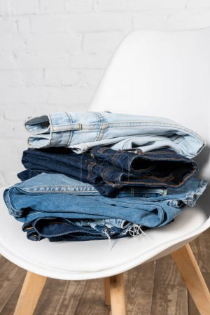 Photo for Stack of different denim garments on white chair near brick wall - Royalty Free Image
