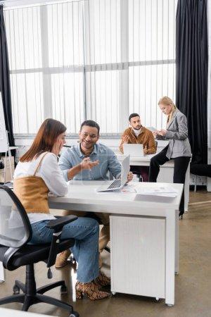 Photo pour Gens d'affaires multiculturels travaillant avec des appareils au bureau - image libre de droit