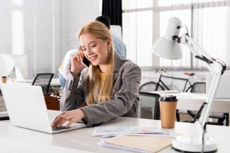 Photo pour Femme d'affaires souriante utilisant un ordinateur portable et parlant sur smartphone près des documents et de la lampe dans le bureau - image libre de droit