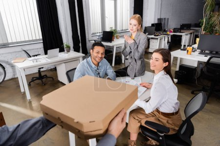 Photo for Smiling multiethnic business people looking at delivery man with pizza boxes on blurred foreground - Royalty Free Image