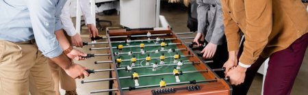 Cropped view of business people playing table soccer in office, banner