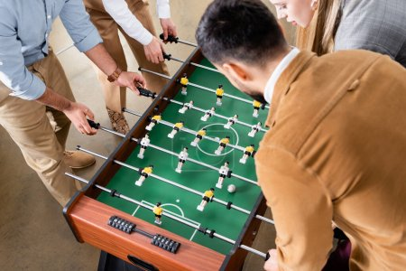 Overhead view of business people playing table soccer with colleagues in office