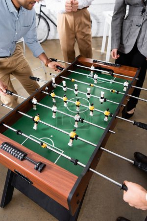 Cropped view of businessman playing table soccer near colleagues