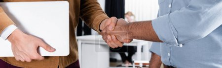 Photo for Cropped view of businessmen with laptop handshaking in office, banner - Royalty Free Image