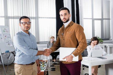 Photo pour Des hommes d'affaires multiethniques serrent la main et regardent la caméra au bureau - image libre de droit