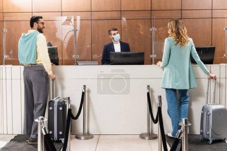 Photo pour Couple interracial avec valises debout près du gestionnaire dans le masque médical dans le hall de l'hôtel - image libre de droit