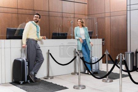 Photo pour Couple interracial joyeux avec ponçage des bagages près de la réception à l'hôtel - image libre de droit