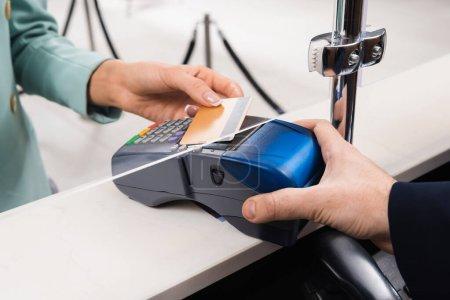 Photo pour Vue recadrée du terminal de paiement de l'exploitation gestionnaire près de la femme avec carte de crédit à l'hôtel - image libre de droit
