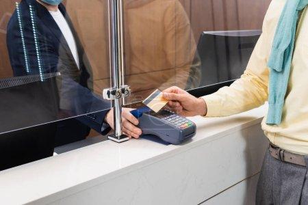 Photo pour Vue recadrée de l'homme payant par carte de crédit près du gestionnaire avec terminal de paiement à l'hôtel - image libre de droit