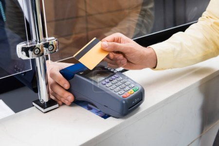 Cropped view of man holding credit card near hotel manager with terminal