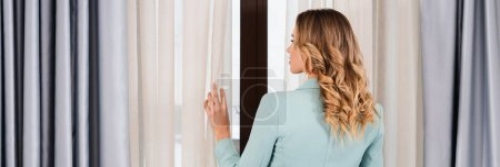 Photo pour Vue arrière de la femme tenant rideau près de la fenêtre dans la chambre d'hôtel, bannière - image libre de droit