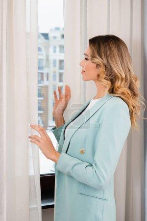 Photo pour Vue latérale de la jeune femme regardant la fenêtre dans la chambre d'hôtel - image libre de droit